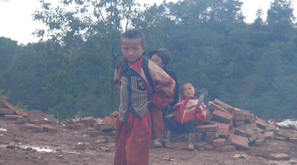 大凉山博爱小学一名小学生 看着新建的学校